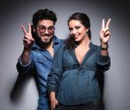 Jeunes couples heureux faisant le signe de victoire Images stock