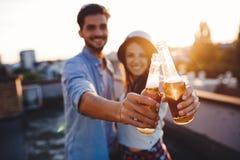 Jeunes couples heureux grillant avec de la bière dehors Photographie stock