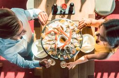 Jeunes couples heureux grillant pendant le dîner romantique à un restaurant à la mode images stock