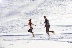 Jeunes couples heureux insouciants ayant l'amusement ensemble dans la neige Photo stock