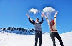 Jeunes couples heureux insouciants ayant l'amusement ensemble dans la neige Images stock