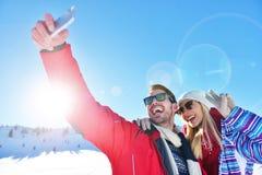 Jeunes couples heureux insouciants ayant l'amusement ensemble dans la neige Photos libres de droits