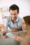 Jeunes couples heureux jouant avec des smartphones à la maison Photo libre de droits