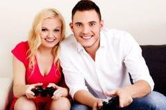 Jeunes couples heureux jouant des jeux vidéo Photographie stock libre de droits