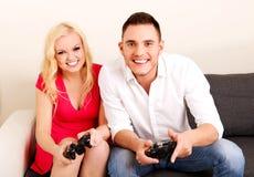 Jeunes couples heureux jouant des jeux vidéo Image libre de droits
