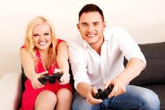 Jeunes couples heureux jouant des jeux vidéo Photo stock