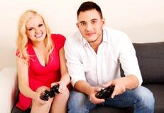 Jeunes couples heureux jouant des jeux vidéo Photos libres de droits