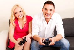 Jeunes couples heureux jouant des jeux vidéo Images stock