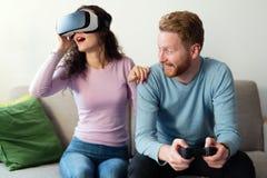 Jeunes couples heureux jouant des jeux vidéo avec des casques de réalité virtuelle Photos stock