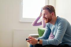 Jeunes couples heureux jouant des jeux vidéo avec des casques de réalité virtuelle Images stock
