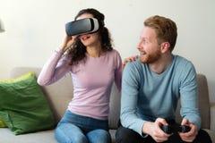 Jeunes couples heureux jouant des jeux vidéo avec des casques de réalité virtuelle Photographie stock