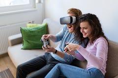 Jeunes couples heureux jouant des jeux vidéo avec des casques de réalité virtuelle Photo stock