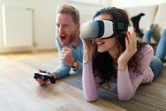 Jeunes couples heureux jouant des jeux vidéo avec des casques de réalité virtuelle Photographie stock libre de droits