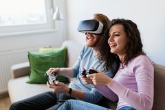 Jeunes couples heureux jouant des jeux vidéo avec des casques de réalité virtuelle Photo libre de droits