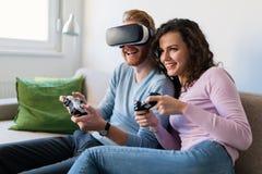 Jeunes couples heureux jouant des jeux vidéo avec des casques de réalité virtuelle Image stock