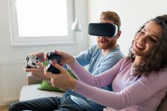 Jeunes couples heureux jouant des jeux vidéo avec des casques de réalité virtuelle Photos libres de droits