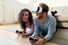 Jeunes couples heureux jouant des jeux vidéo avec des casques de réalité virtuelle Image libre de droits
