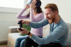 Jeunes couples heureux jouant des jeux vidéo avec des casques de réalité virtuelle Images libres de droits