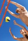 Jeunes couples heureux jouant le volleyball Images libres de droits