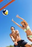 Jeunes couples heureux jouant le volleyball Images stock