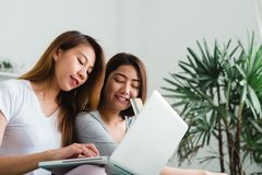 Jeunes couples heureux lesbiens asiatiques des femmes LGBT se reposant sur le sofa achetant en ligne utilisant l'ordinateur porta Photo libre de droits