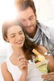 Jeunes couples heureux mangeant de la glace sur la plage d'été image libre de droits
