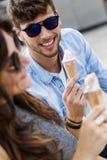 Jeunes couples heureux mangeant la crème glacée dans la rue Photographie stock libre de droits