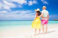 Jeunes couples heureux marchant et ayant l'amusement par la plage Image stock