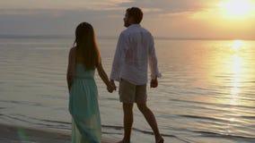 Jeunes couples heureux marchant près de la mer sur le coucher du soleil Concept de l'amour banque de vidéos