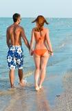 Jeunes couples heureux marchant tenant des mains sur le bord de la mer Photo stock