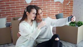 Jeunes couples heureux montrant des clés du nouvel appartement prenant le selfie utilisant le tir moyen de smartphone clips vidéos