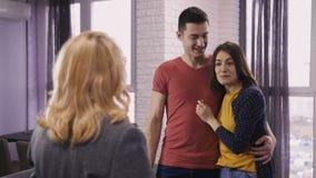 Jeunes couples heureux obtenant des clés au nouvel appartement banque de vidéos