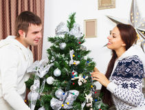 Jeunes couples heureux par l'arbre de Cristmas Photographie stock
