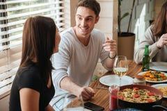 Jeunes couples heureux parlant à la table à la maison Photo libre de droits