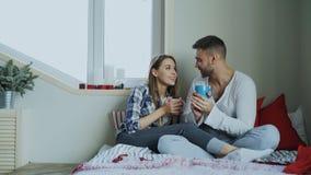 Jeunes couples heureux parlant et riant tout en se reposant dedans sur le coffe de lit et de boissons pendant le matin à la maiso Photographie stock