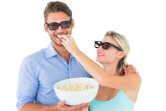 Jeunes couples heureux portant les lunettes 3d mangeant du maïs éclaté Photo libre de droits