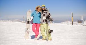 Jeunes couples heureux posant avec leurs surfs des neiges Images stock