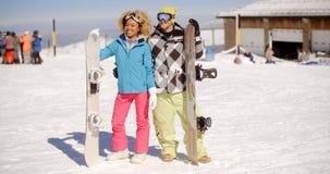 Jeunes couples heureux posant avec leurs surfs des neiges Photographie stock