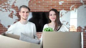 Jeunes couples heureux posant tenant déballer la boîte avec des affaires pendant la caméra de regard en mouvement banque de vidéos