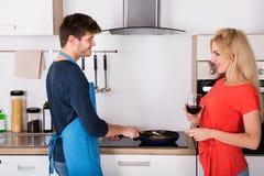 Jeunes couples heureux préparant le dîner dans la cuisine Image libre de droits