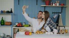 Jeunes couples heureux prenant le portrait de selfie tout en prenant le petit déjeuner dans la cuisine à la maison image libre de droits