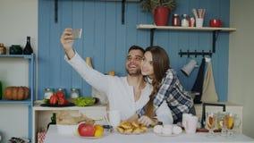 Jeunes couples heureux prenant le portrait de selfie tout en prenant le petit déjeuner dans la cuisine à la maison photographie stock libre de droits
