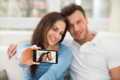Jeunes couples heureux prenant un selfie Photos libres de droits