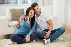 Jeunes couples heureux prenant un selfie Photos stock