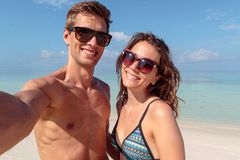Jeunes couples heureux prenant un selfie, l'eau bleue claire comme fond ?treinte image stock