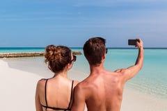 Jeunes couples heureux prenant un selfie ?le tropicale comme fond photos stock
