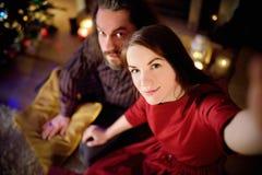 Jeunes couples heureux prenant une photo de lui-même par une cheminée sur Noël Images libres de droits