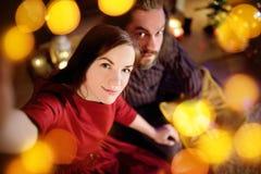 Jeunes couples heureux prenant une photo de lui-même par une cheminée sur Noël Photographie stock