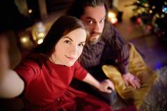 Jeunes couples heureux prenant une photo de lui-même par une cheminée sur Noël Image libre de droits