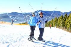 Jeunes couples heureux regardant en montagnes neigeuses tenant le ski Foyer sélectif photos stock
